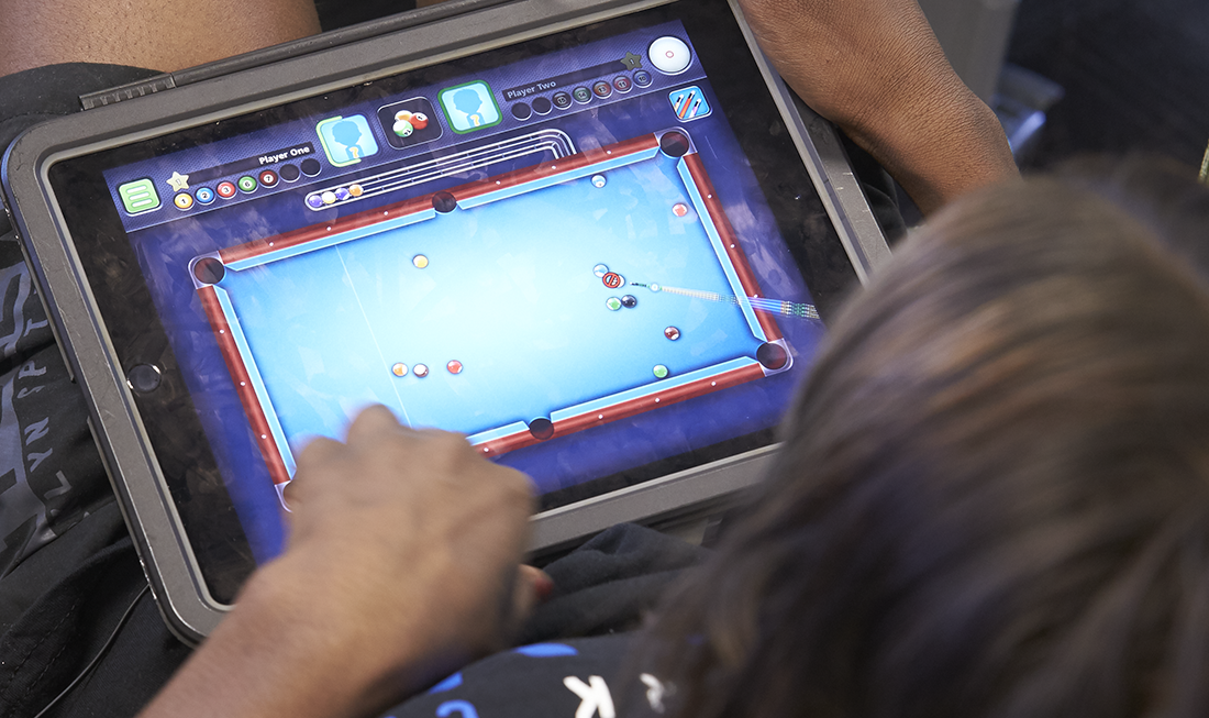 A person playing a game on a tablet.