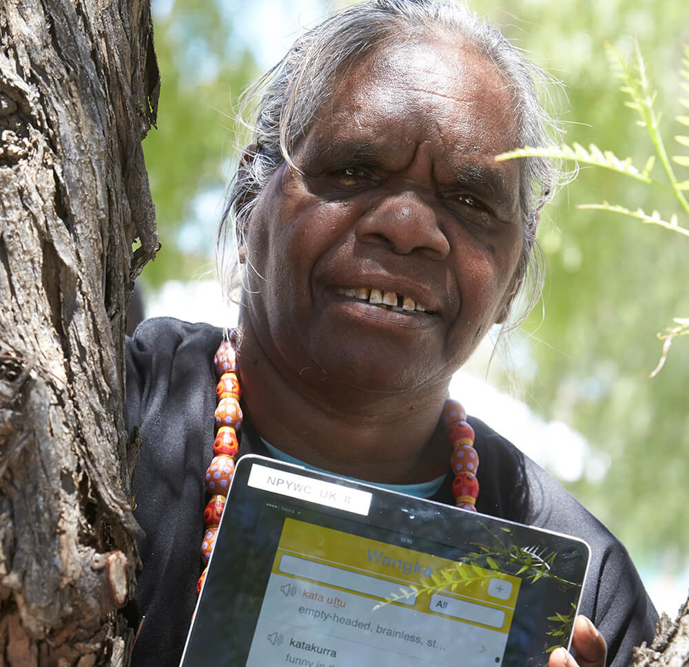 Image of an aboriginal lady holding a tablet or iPad with the language app on the screen