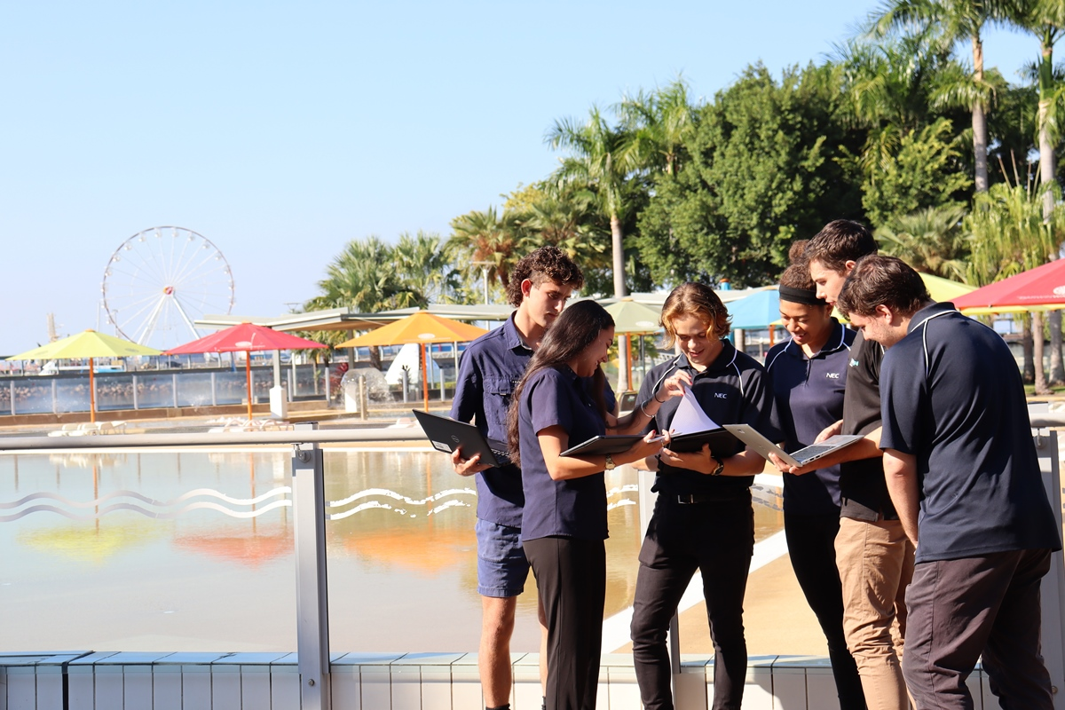 Students looking over some paperwork and laptops in an outdoor water park in the background